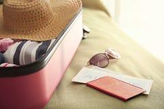 Dokumente und offener Koffer mit verpackten Sachen auf Bett lizenzfreies stockbild