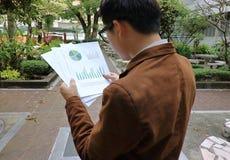 Dokumente werden vom jungen hübschen Geschäftsmann am allgemeinen Park gelesen stockfotos