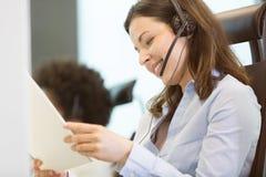 Dokumenterar den bärande telefonhörlurar med mikrofon för den unga affärskvinnan, medan läs-, i regeringsställning Arkivbilder
