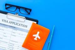 Dokumenty dla podróży zagranicznej Wniosek wizowy forma, pióro, paszport pokrywa z samolotową sylwetką na błękitnym tło wierzchoł obraz stock