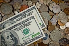 100 Dolar-bankbiljetten en muntstukken van verschillende landen Stock Fotografie