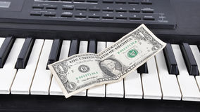 Dolar lying on the keys of old synthesizer Stock Photos