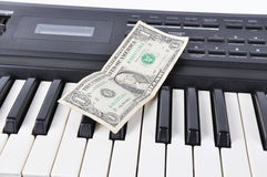 Dolar lying on the keys of old synthesizer Stock Photo