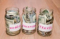 Dolar w szklanym słoju z domem, samochód, edukacja, poślubia podróży etykietki pieniężnego pojęcie zdjęcia royalty free