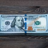 Dolarowi banknoty kłamają przy drewnianym tłem fotografia royalty free