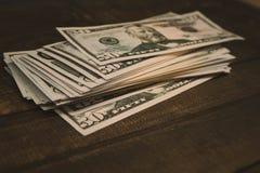 Dolarowi banknoty k?amaj? przy drewnianym t?em fotografia royalty free