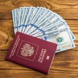 Dolarowi banknoty w fan i paszporcie przy drewnianym t?em fotografia stock
