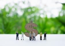 Dolarowy znak za miniaturowym biznesmena handshaking, dyskutuje Zdjęcie Royalty Free