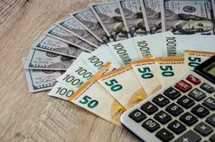 Dolary, euro i kalkulator na drewnianym tle, i obrazy royalty free