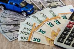 Dolary, euro, kalkulator i zabawkarski błękitny samochód na drewnianym tle, obrazy royalty free