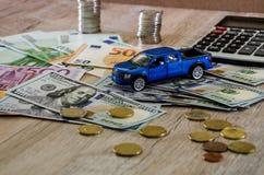 Dolary, euro, monety, kalkulator i zabawkarski błękitny samochód na drewnianym tle, fotografia royalty free