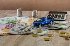 Dolary, euro, monety, kalkulator i zabawkarski błękitny samochód na drewnianym tle, zdjęcia royalty free