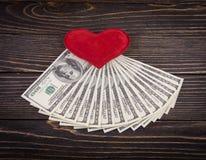 Dolary i czerwona ręka na drewnianym starym tle Obrazy Royalty Free