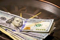 Dolary kłamają na dużym zegarze który liczy czas, Czas zarabiać pieniądze Czas jest money_ obraz royalty free