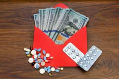 Dolary waluty w kopercie przeciw rozrzuconym pastylkom, pigułki, kapsuły, zakup lekarstwa fotografia stock