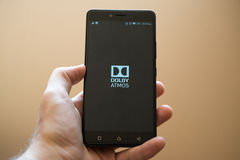 Dolby Atmos. Nitra, Slovakia, april 3, 2017: Man holding smartphone with Dolby Atmos application on the screen royalty free stock photography