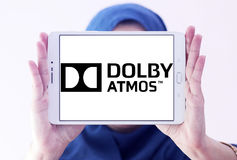 Dolby atmos sound technology logo. Logo of dolby atmos sound technology on samsung tablet holded by arab muslim woman. Dolby Atmos is the name of a surround stock photo