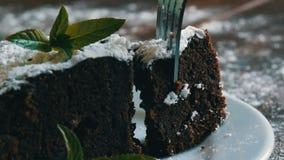 Dolce al forno casalingo del brownie del cioccolato attutito con zucchero in polvere su un piatto bianco decorato con le foglie d video d archivio