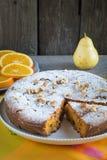 Dolce alle carote delizioso dai dadi, uva passa con la decorazione dell'arancia, pera su un piatto bianco Stile rustico Fotografie Stock