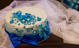Dolce bianco con i nastri blu ed i fiori blu Immagine Stock Libera da Diritti