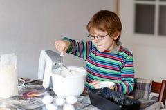 Dolce biondo divertente di cottura del ragazzo del bambino all'interno Fotografie Stock Libere da Diritti