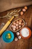 Dolce bollente in cucina rurale - uova degli ingredienti di ricetta della pasta, farina, zucchero sulla tavola di legno d'annata  Immagini Stock