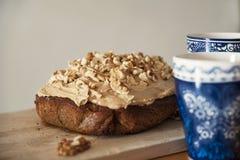 Dolce casalingo delizioso di caffè e della noce con le tazze calde della bevanda da parte Fotografia Stock