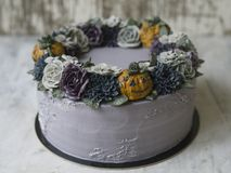 Dolce crema grigio decorato con i fiori e le zucche scuri del buttercream su fondo rustico Dolce di Halloween Dolce unsual nero c immagine stock