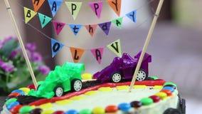 dolce cremoso decorato con le automobili del giocattolo stock footage