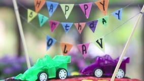 dolce cremoso decorato con le automobili del giocattolo video d archivio