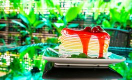 Dolce dolce del crêpe dell'arcobaleno con la guarnizione della salsa della fragola sul piatto sui precedenti verdi dell'albero de immagini stock