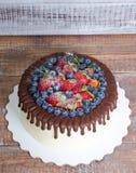 Dolce del gocciolamento di colore del cioccolato con i mirtilli e le fragole e Fotografie Stock