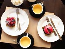 Dolce del lampone-pistacchio e del lampone con le tazze di t? sulla tavola fotografia stock libera da diritti