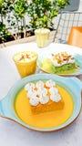 Dolce del latte del pistacchio e dello zafferano tre e tazza di cappuccino Fotografia Stock