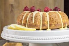 Dolce del limone glassato della glassa gialla dello zucchero e dei lamponi rossi, Fotografia Stock