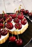 Dolce della ciliegia e un mazzo di ciliege sulla tavola Immagini Stock