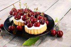 Dolce della ciliegia e un mazzo di ciliege sulla tavola Fotografia Stock Libera da Diritti