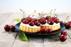 Dolce della ciliegia e un mazzo di ciliege sulla tavola Immagine Stock Libera da Diritti