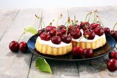 Dolce della ciliegia e un mazzo di ciliege sulla tavola Fotografia Stock