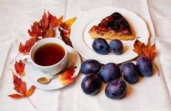 Dolce della prugna e tazza di tè Immagine Stock