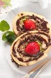 Dolce dello swiss roll del cioccolato con le fragole Fotografia Stock
