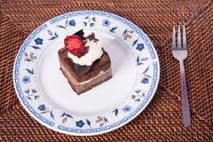 Dolce di cioccolato con la fragola, la forcella e la mano Fotografia Stock