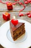 Dolce di cioccolato con le candele sotto forma di un cuore Fotografia Stock
