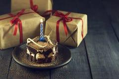 Dolce di cioccolato con una candela ed i regali Buon compleanno, carta Cartolina d'auguri di feste Fotografia Stock