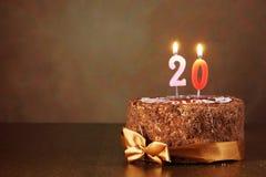 Dolce di cioccolato di compleanno con le candele brucianti come numero venti immagini stock