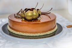 Dolce di cioccolato dorato con il fiore e le perle Fotografia Stock