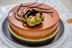 Dolce di cioccolato dorato con il fiore e le perle Immagine Stock