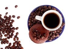 Dolce di cioccolato e del caffè nero e chicchi di caffè su una vista superiore isolata fondo bianco immagine stock libera da diritti