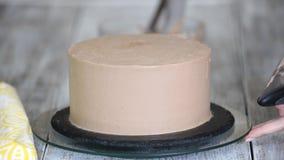 Dolce di cioccolato Il confettiere copre la crema cremosa del dolce di cioccolato E Borsa della pasticceria con crema video d archivio