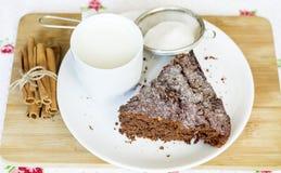 Dolce di cioccolato in un piatto ed in una tazza bianchi con latte Fotografie Stock
